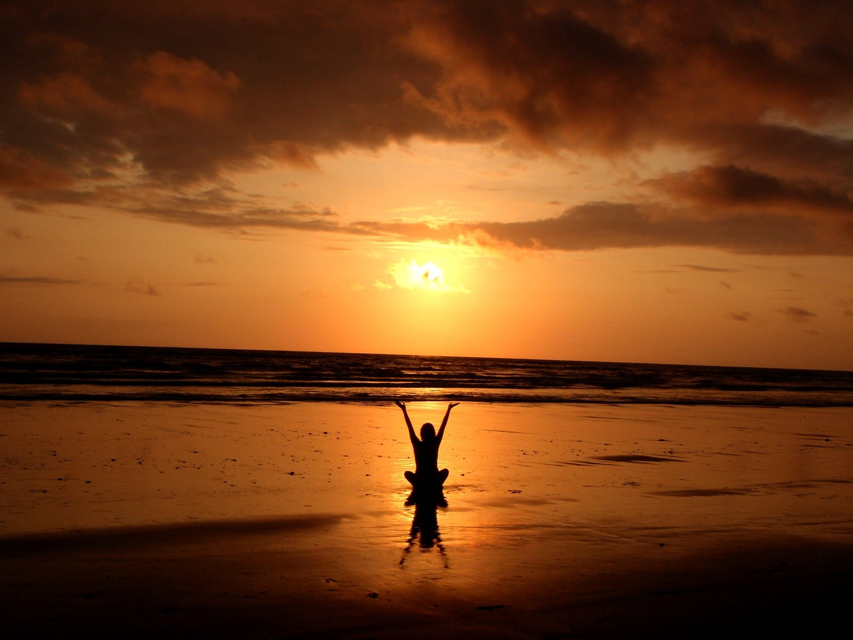 Photo of the back of a woman in shadow form, sitting in lotus position with her hands up towards the sky. The background includes a sunset, the ocean, and the beach.