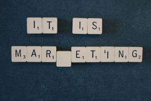 """Photo of scrabble tiles that say """"It is marketing,"""" with the k missing."""