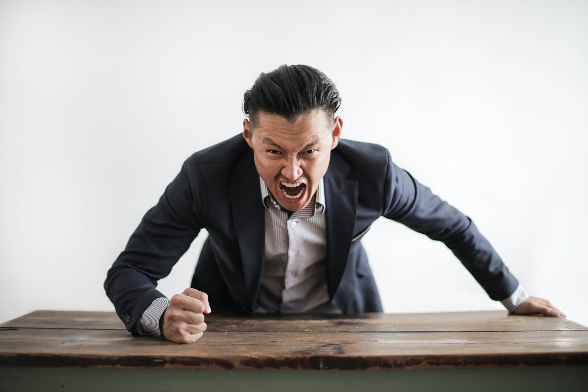 image of man yelling with his fist on a desk, probably pounding on it to annunciate his words.