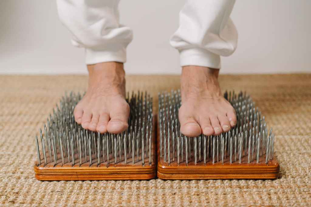 Picture of person standing, barefoot, on nails.